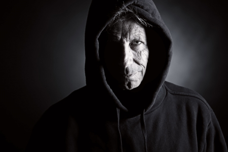 scary face: Low Key Shot of an Intimidating Senior Male in Hooded Top