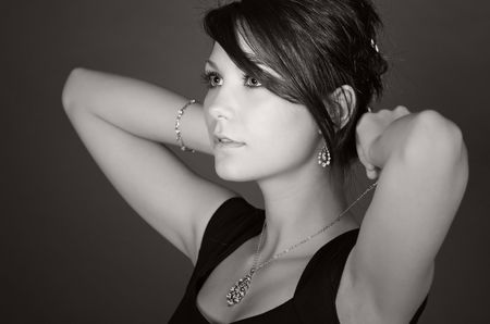 黒と白のショットは見事な十代モデルに置くことの灰色の背景に対して彼女のネックレス