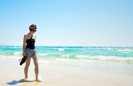 sun drenched: Shot of an Attractive Brunette Walking Along a Sun Drenched Beach