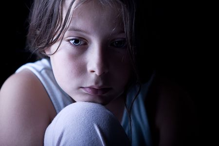 sad faces: Powerful Low Key Shot of a Young Child Looking Sad