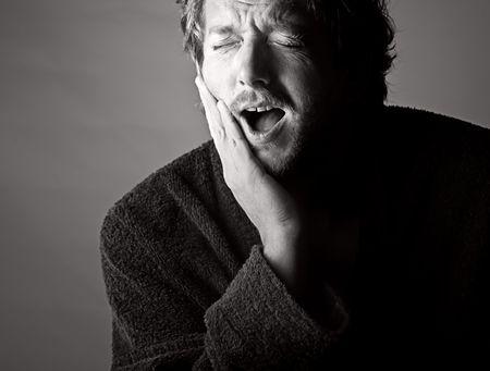 mal di denti: Drammatico bianco e nero Shot of a Man in Pain azienda la mascella. Mal di denti!