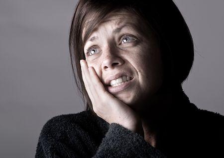 dolor  de diente: Tiro de una mujer con dolor de muelas contra Grey Foto de archivo