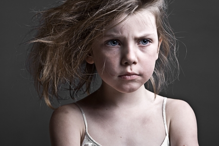 nine years old: Powerful Shot of a Messy Child against a Grey Background
