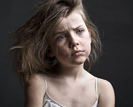 maltrato infantil: Potente shot de un ni�o desordenado contra un fondo gris Foto de archivo