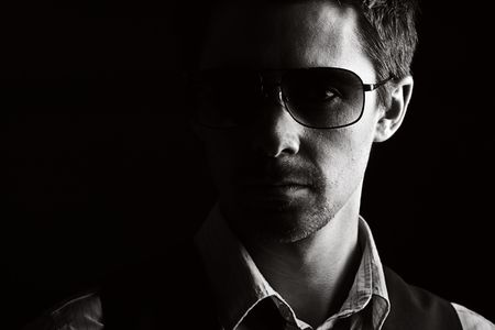 intimidating: Low Key Shot of a Handsome Male in Sunglasses