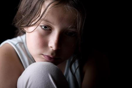 fille triste: Puissant Low Key Shot d'un jeune enfant l'air triste