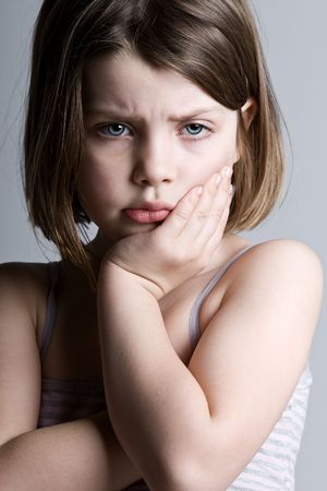Shot of a Sad Looking Child against a Grey Background Stock Photo