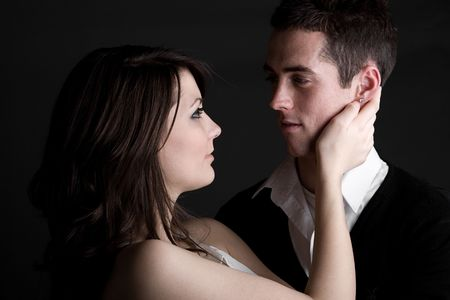 Shot of a Young Couple Embracing against Dark Background photo