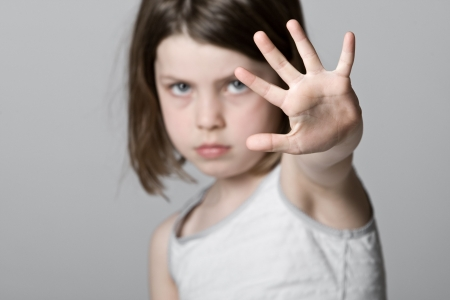 fear child: Powerful Shot of a Child with her Hand Up