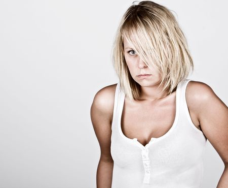 unkempt: Powerful Shot of a Pensive Blonde Female in White Vest against Grey Background
