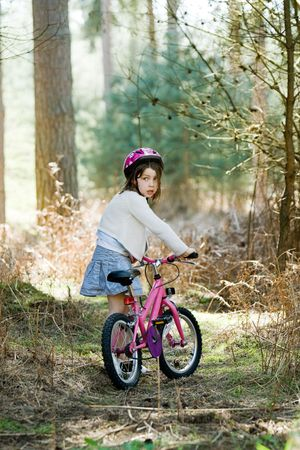 Shot of a Young Girl with her Bike in the Forest photo