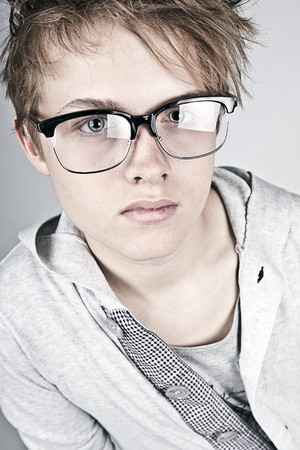 geeky: Shot of a Geeky Looking Teenager against Grey Background Stock Photo