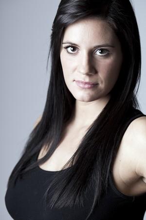 Shot of a Beautiful Brunette Girl In Black Vest against Grey photo