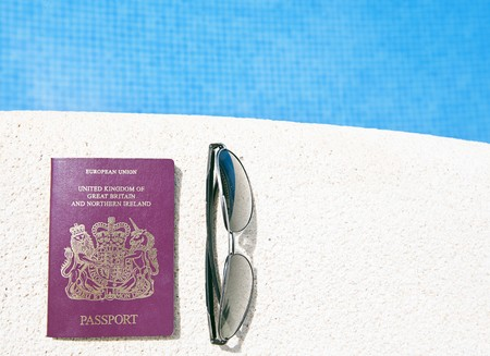 noone: Shot of a Passport and Sunglasses on the Edge of a Swimming Pool Stock Photo