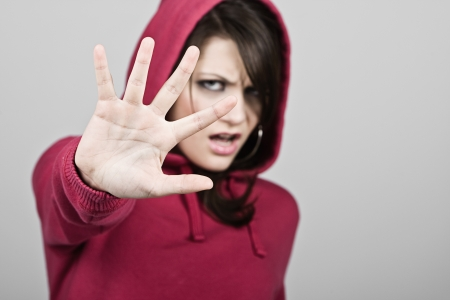 hoody: Hooded Teenage Girl Holding Hand Up - STOP Stock Photo