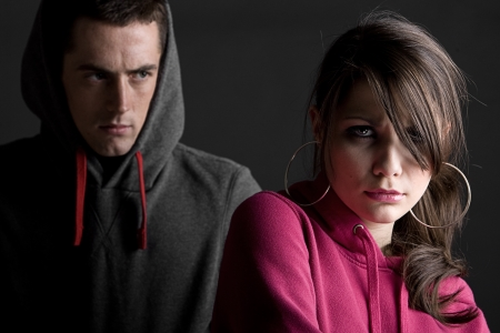 intimidating: Two Hooded Teenagers against Dark Background