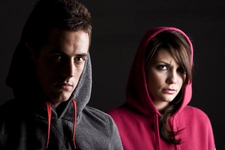 menacing: Two Hooded Teenagers against Dark Background