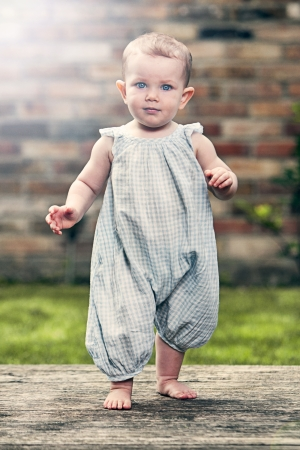 Shot of a Pretty Baby Girl in Blue Jumpsuit in Garden Stock Photo