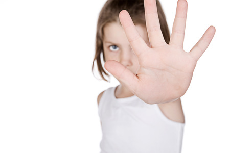 Shot of a Cute LIttle Girl Hiding Behind her Hand photo