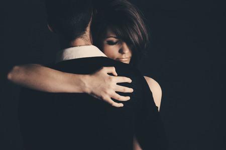 ojos tristes: Tiro oscuro de un Abrazar Pareja joven Foto de archivo