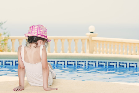 Shot of a Young Girl Sitting by the Pool photo
