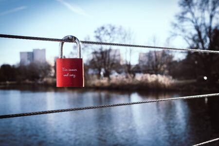 Red padlock, love lock on a bridge