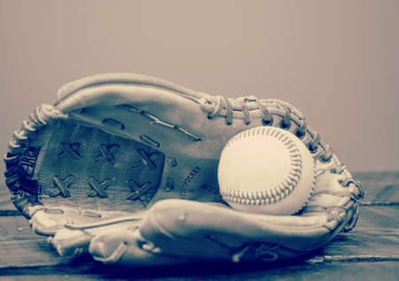 Greyscale filter on open baseball glove with baseball in the mitt.