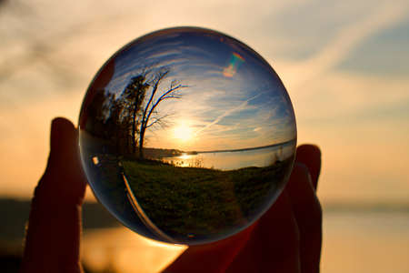 Reflection of sunset over water in a crystal ball, held by a hand
