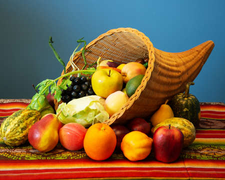 A cornucopia filled with fake fruits and vegetables. Stock Photo