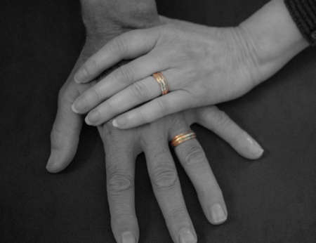 Two hands clasp, older married coupled, focus on wedding rings. Reklamní fotografie
