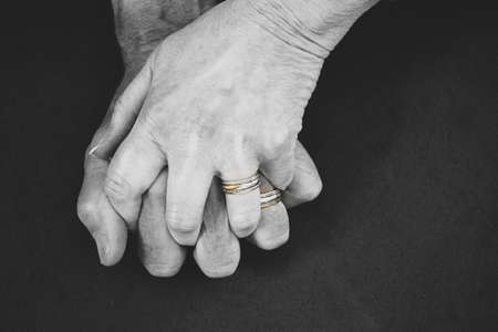 Two hands clasp, older married coupled, focus on wedding rings.
