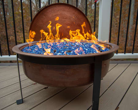 Lit copper Fire Pit on backyard porch, with blue crystals.