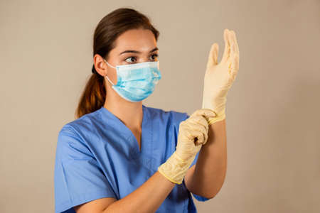 Brunette nurse in blue shirt putting on rubber gloves. Caucasian girl touching her hand with fingers on light background. Horizontal portrait of medical worker using hygienic protection.