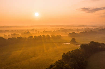 Sun rising above riparian forest in summer from drone. Outdoor scenery with sky and clouds in the morning illuminated by soft orange light. Misty natural environment from aerial point of view.
