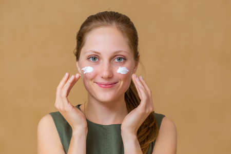 Beautiful young woman applying facial cosmetics with her hands. Concept of healthy lifestyle with skin care. Cheerful female with moisturizer on her body facing camera.
