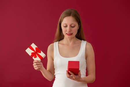 Embarrassed woman looking on a present on red background. Disappointed female with box in hands. Blonde girl confused by valentine gift.