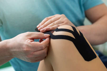 Physiotherapist applying tape to patient knee.