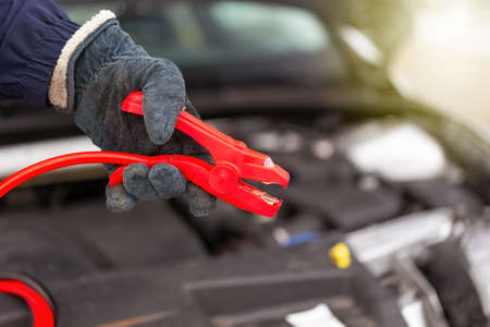 Person holding red jumper cable next to car in close up