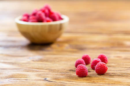 Pile of fresh raspberries lying on table with full bowl in background
