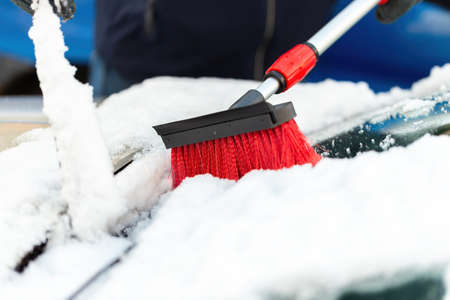 Person with broom brushing snow from windshield in close-up Фото со стока