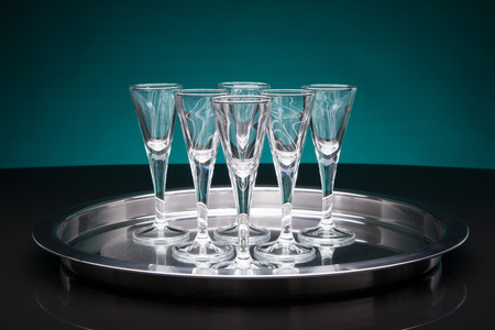 silver tray: shot glasses on a silver tray with a blueish background