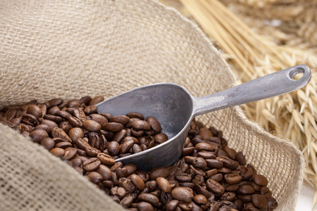 poured: coffee beans and a silver shovel lying in a sack