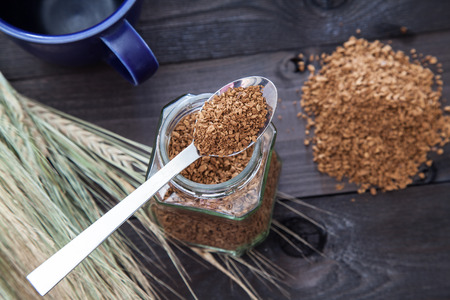 caffeinated: Instant coffee on a spoon that lies on a glass jar