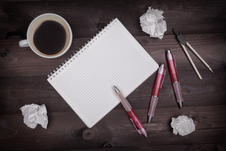 Top view of idea concept with pencils, notepad, coffee cup and crumpled paper on a black wooden table