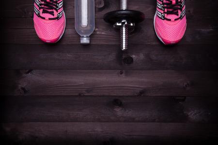 levantamiento de pesas: Equipo de deporte. Zapatillas de deporte, agua y una pesa de gimnasia en un fondo de madera negro Foto de archivo