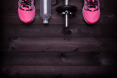 Sport equipment. Sneakers, water and a dumbbell on a black wooden background Imagens