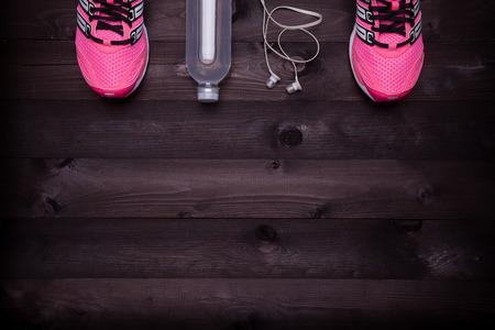 스포츠 장비. 검은 나무 배경에 운동화, 물, 이어폰 스톡 콘텐츠