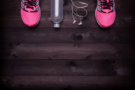Sport equipment. Sneakers, water and earphones on a black wooden background