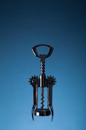 Corkscrew of metal against a blue background. Wine list concept. Stok Fotoğraf