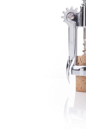 corcho: Sacacorchos de tornillos de metal en un corcho contra un fondo blanco. Lista concepto de vino.